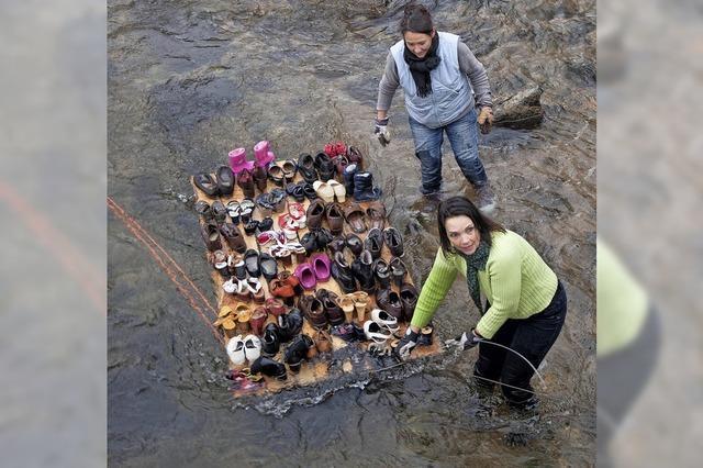 Kunstaktion: Ein Floß mit Schuhen treibt in der Elz