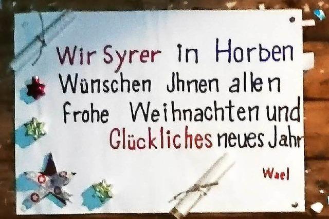Syrische Flüchtlinge grüßen Horbener mit Schild an der Bushaltestelle