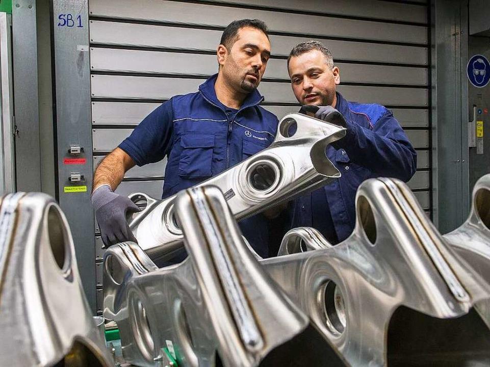 Der syrische Flüchtling Mohammed K. (l.) arbeitet gerade bei Daimler zur Probe.  | Foto: dpa