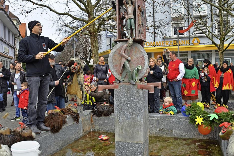 Die Dinkelbergschrate, hier Vorsitzender Jürgen Zöhner mit Besen, staubten am Donnerstag ihre Masken am Narrenbrunnen ab. (Foto: Peter Gerigk)