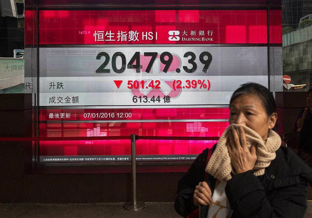 Eine Passantin läuft in Hongkong an ei...rbei, die fallende Börsenkurse zeigt.     Foto: dpa