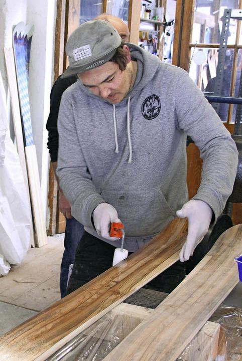EinSchritt nach dem anderen: Florian Baumgärtel lackiert die Bretter.     Foto: dpa
