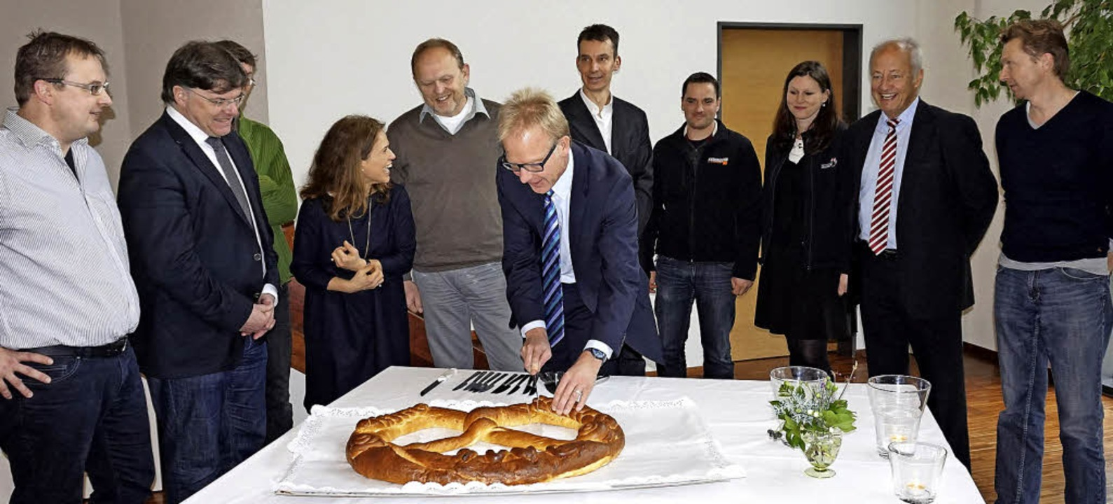 Vertreter der Vereine und des Gemeinde...spannt das erste Stück Neujahrsbrezel.    Foto: Julius Wilhelm Steckmeister