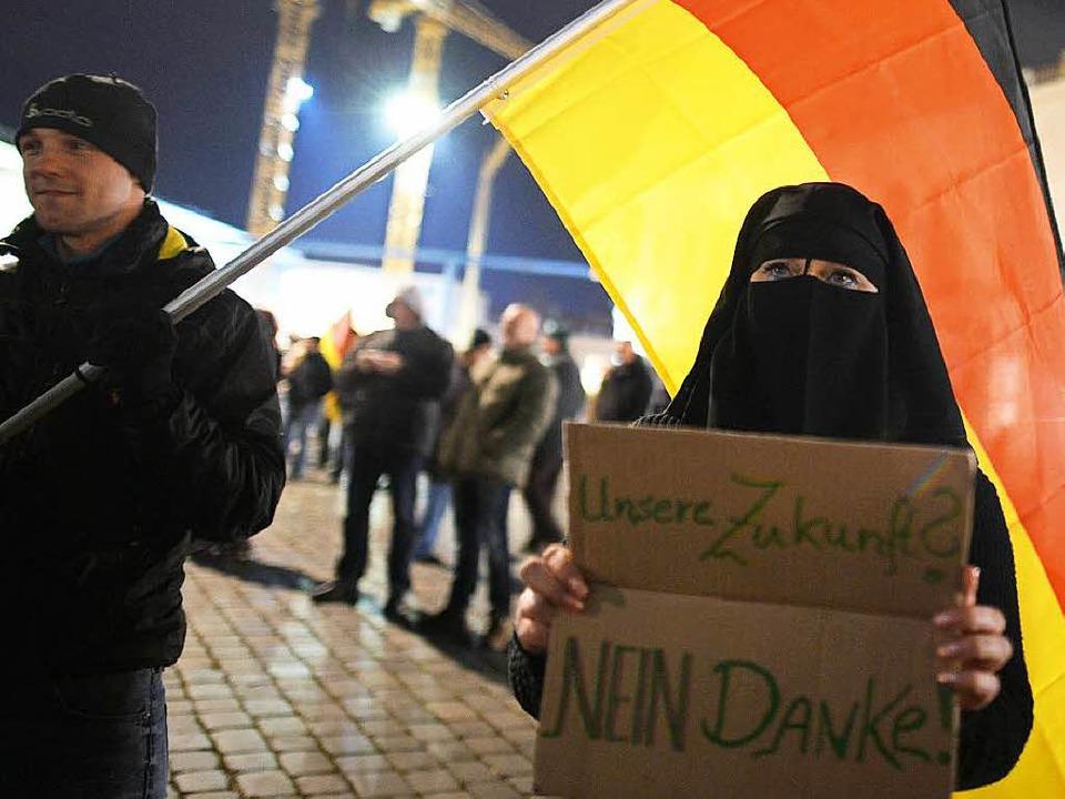 Eine Frau demonstriert während einer Pegida-Kundgebung in Dresden.  | Foto: dpa