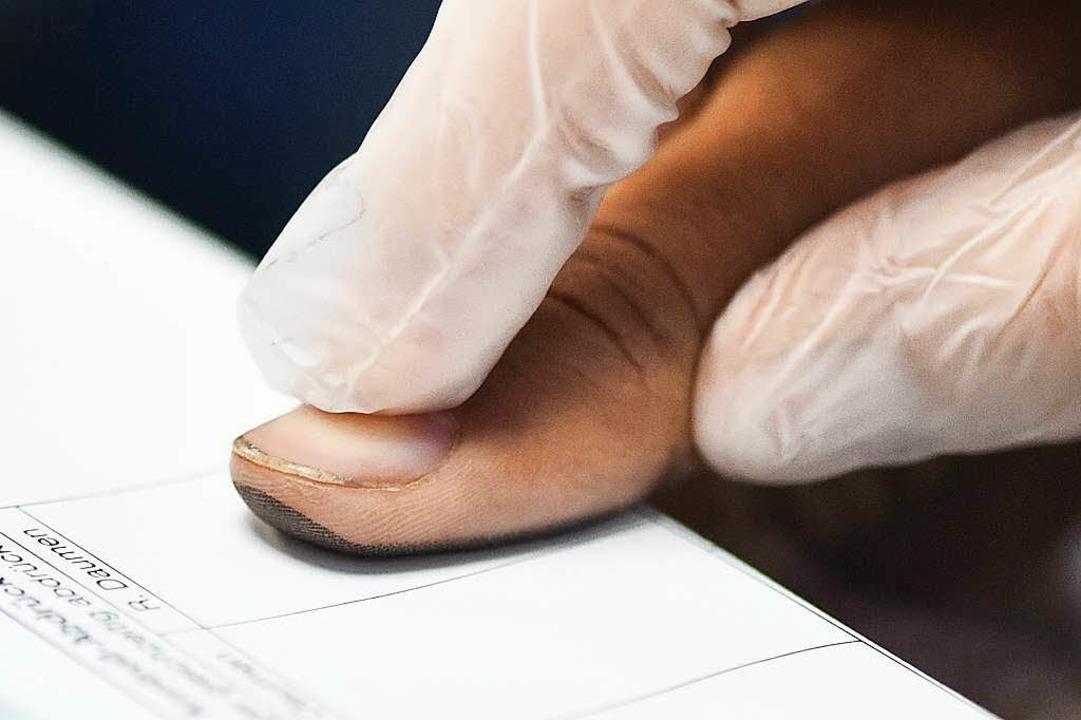 Ein Flüchtling gibt bei seiner Registr...n Heidelberg seinen Fingerabdruck ab.   | Foto: dpa