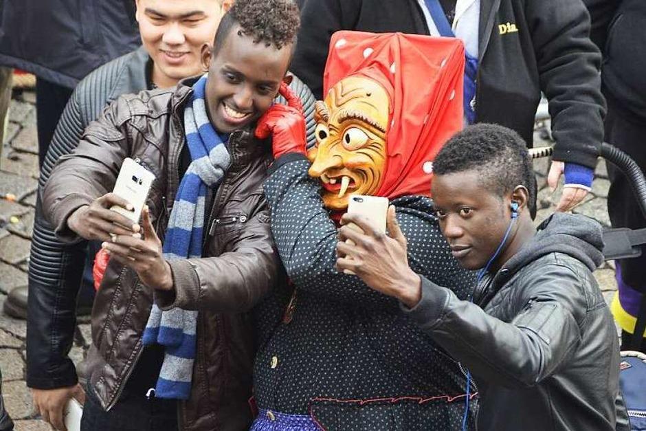 """Selfie mit Offenburger Hexe: Die jungen Flüchtlinge Syedali aus Somalia (l.) und Osman aus dem Senegal haben Spaß an der Offenburger Fasent: """"It's fun!"""" – es ist ein Spaß. (Foto: Helmut Seller)"""