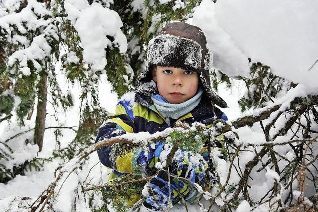 Kinder spielen mit Sachen, die Schnee und Wald gerade hergeben