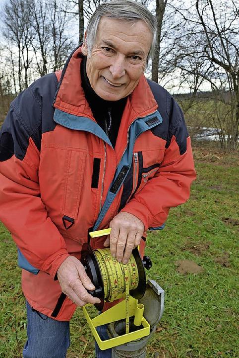 Hartmut Heise beim Messen des Grundwasserpegels   | Foto: Hönig