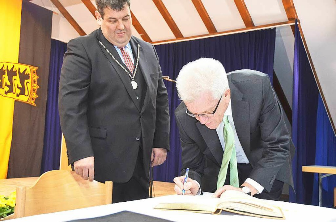 Der Ministerpräsident trägt sich ins Goldene Buch von Schönau ein.  | Foto: Hermann Jacob