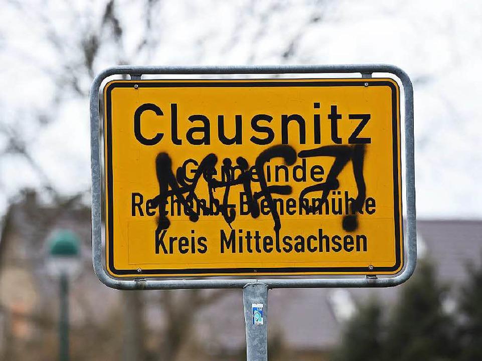 Beschmiert ist das Ortsschild von Clau...nft der ersten Bewohner zu blockieren.  | Foto: dpa