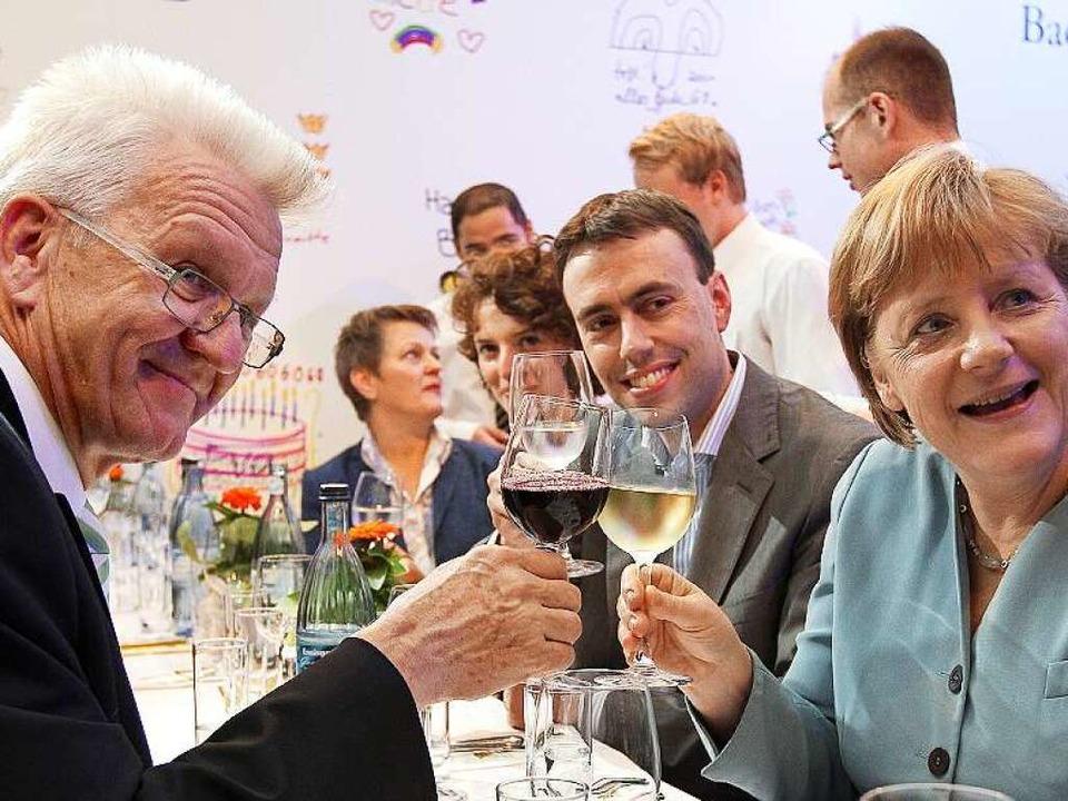 Archivbild: Ministerpräsident Winfried...ndeskanzlerin Angela Merkel stoßen an.    Foto: dpa