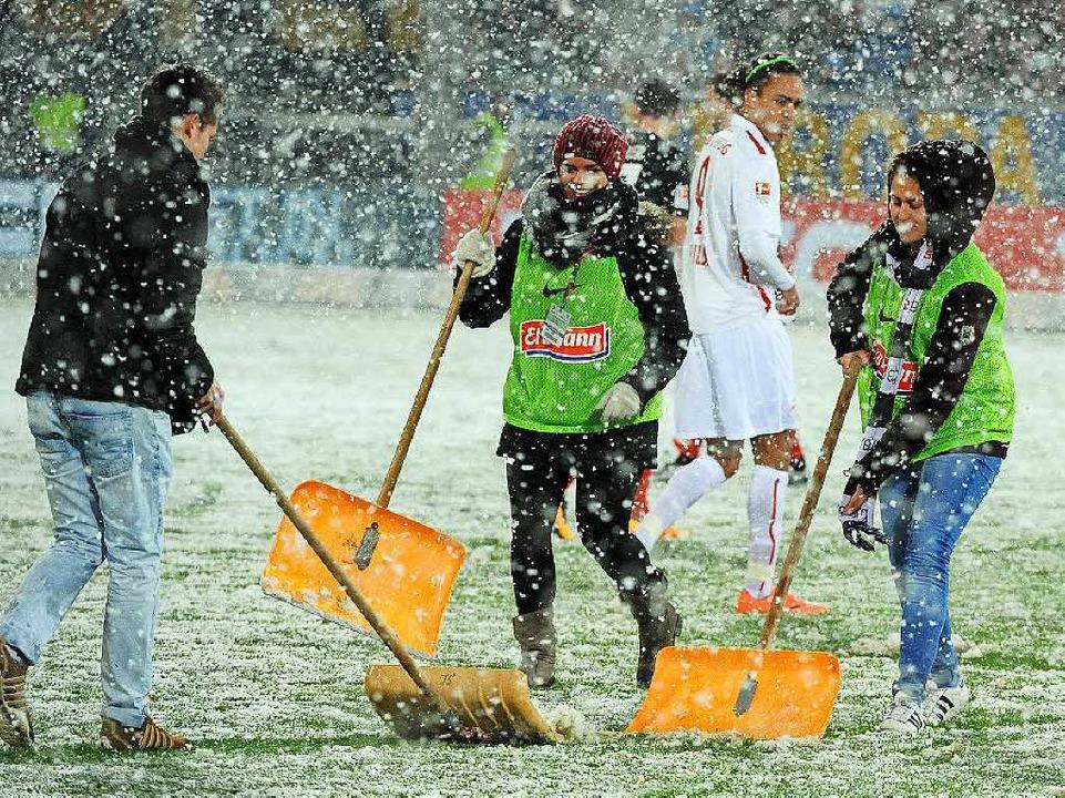 Gemeinsam sind wir stark: Helfer räumen das Spielfeld vom Schnee.  | Foto: Heuberger