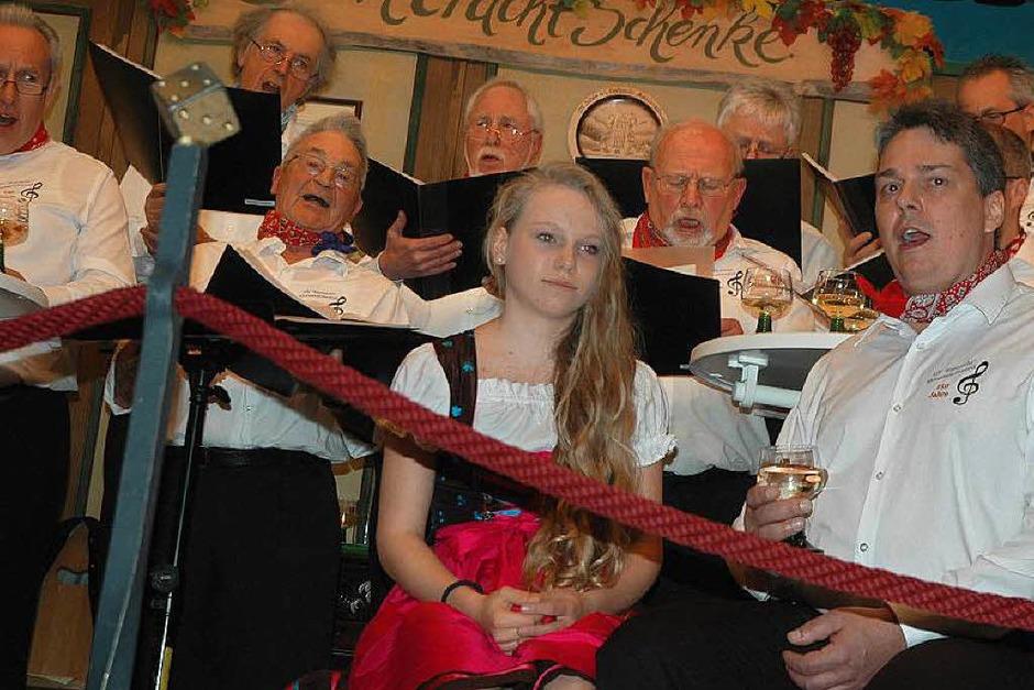 """Die im Lied besungene """"schmucke Magd"""" (Michaela Baur) bringt dem Solisten Rainer Baur – ihrem Vater –  ein Glas Wein. (Foto: Christiane Sahli)"""
