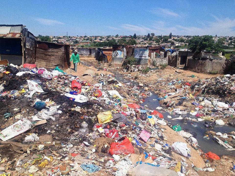 Eine wilde Müllhalde säumt eine der Gassen im Slum.  | Foto: Johannes Dieterich