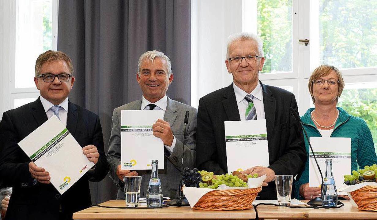 Die Spitzenpolitiker der Grünen und CD...grün-schwarzen Koalitionsvertrag vor.   | Foto: dpa