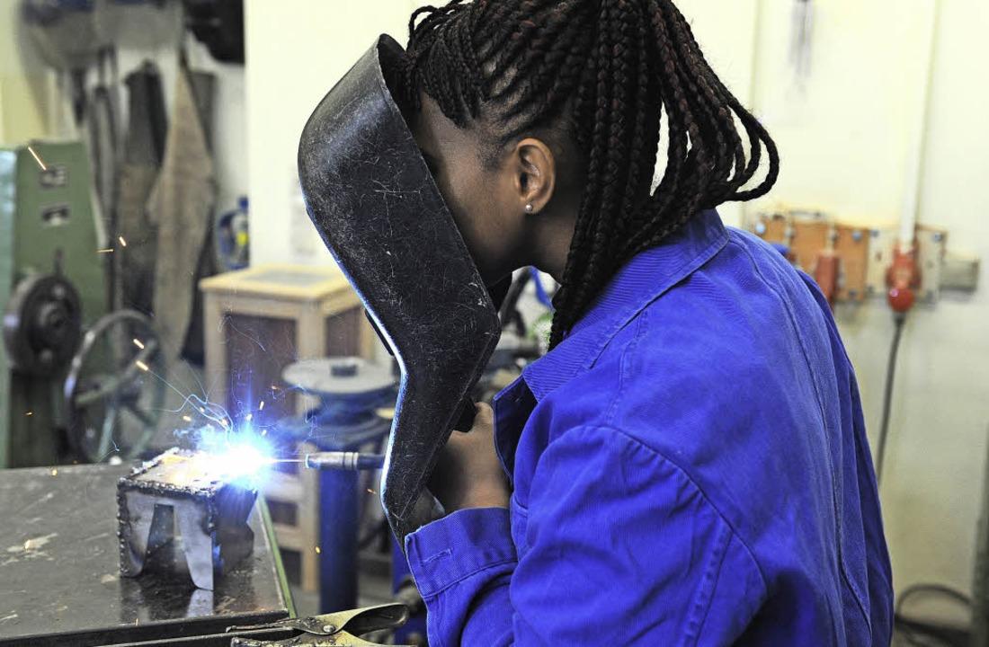 Eine Schülerin aus Guinea übt an einem E-Schweißgerät.     Foto: dpa