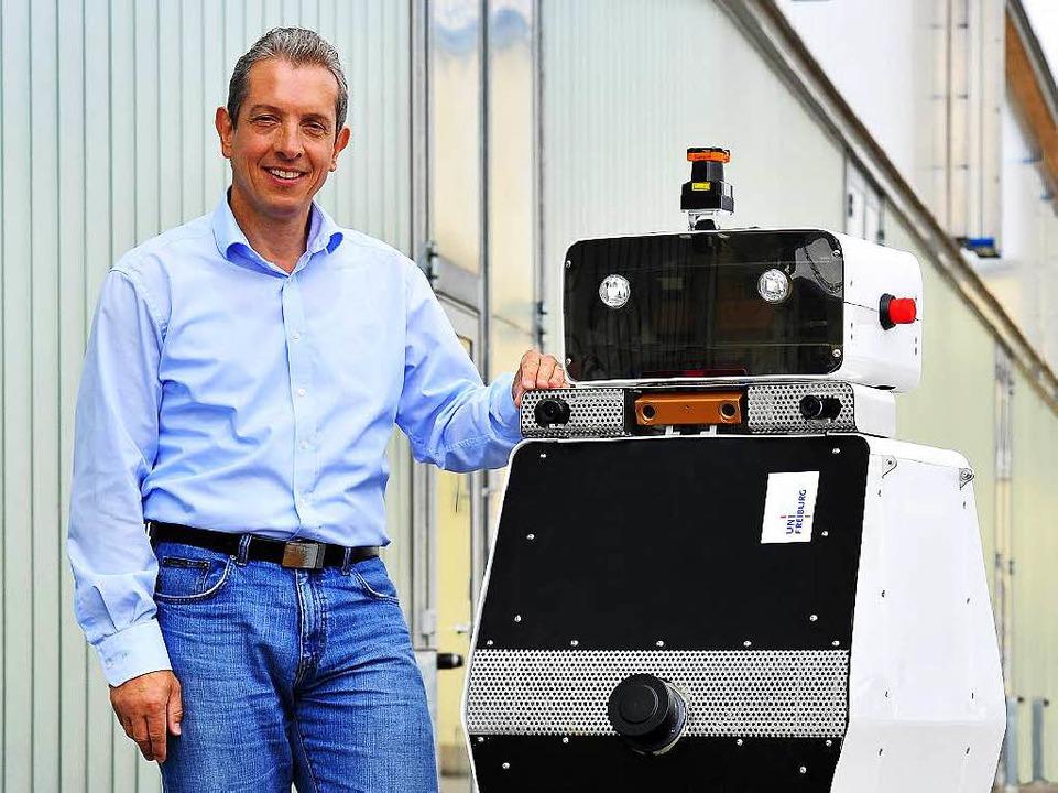 Der Freiburger Forscher Wolfram Burgard mit seinem Roboter Obelix.  | Foto: Thomas Kunz