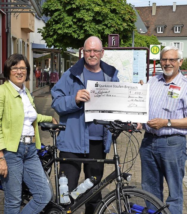 Oli Trelenberg (Bildmitte) radelt für ...n ihm einen Scheck der Stadt Breisach.  | Foto: Voigt