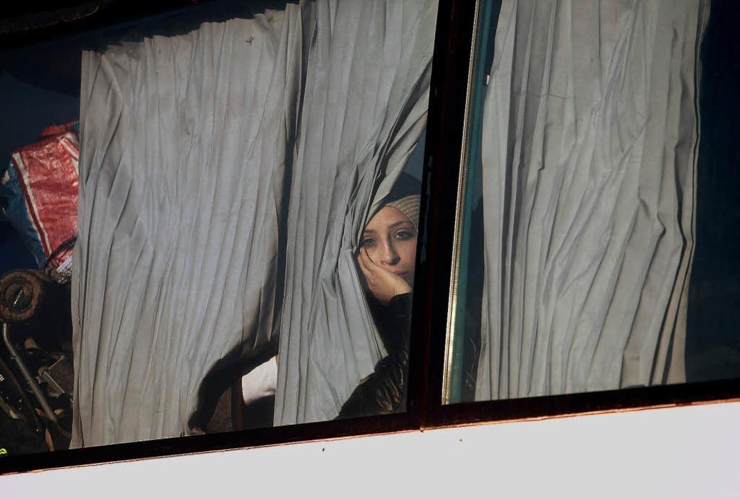 Eine Frau blickt  aus dem Bus, der sie...isierten Camp bei Idomeni wegbringt.    | Foto: afp