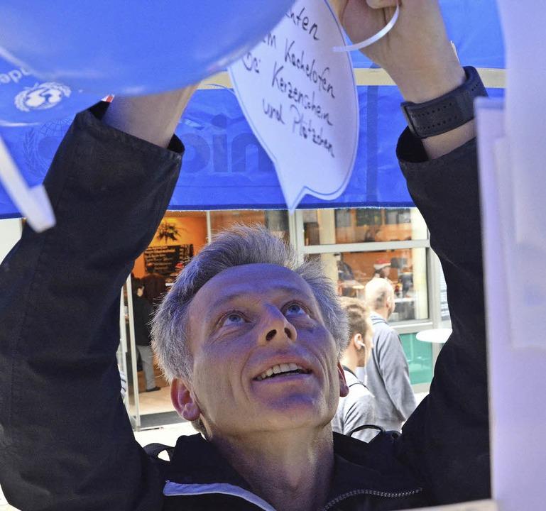 Bürgermeister Michael Wilke bringt eine Papierwolke an.  | Foto: Barbara Ruda