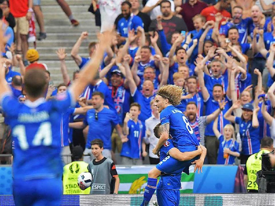 Der isländische Spieler Birkir Bjarnas...) wird von Fans und Spielern bejubelt.  | Foto: dpa