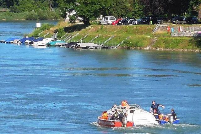 Rettungskräfte holen Sportboot aus dem Rhein