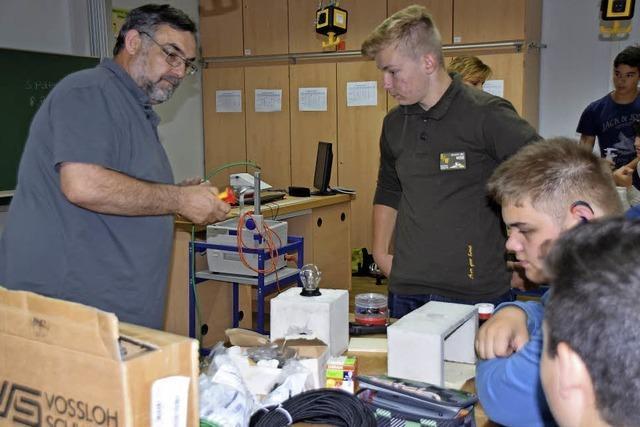 Elektrikfachmann zeigt Schüler Tricks