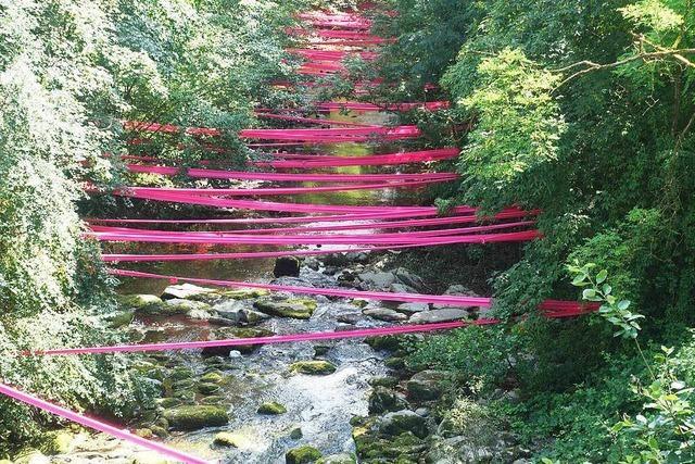 Kunstaktion: Künstler näht Flussufer mit Stoffbändern zusammen