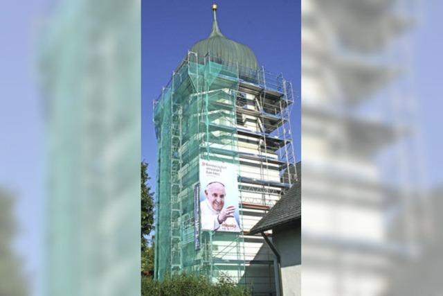 Der Papst lächelt vom Kirchturm