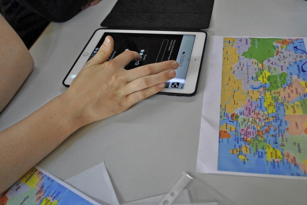 Schüler mit Tablet und Weltkarte beim Geocache-Projekt.   | Foto: Diakonie