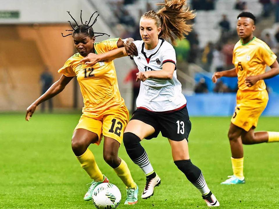 Sara Däbritz im Zweikampf mit  Marjorty Nyaumwe aus dem Simbabwe-Team  | Foto: dpa