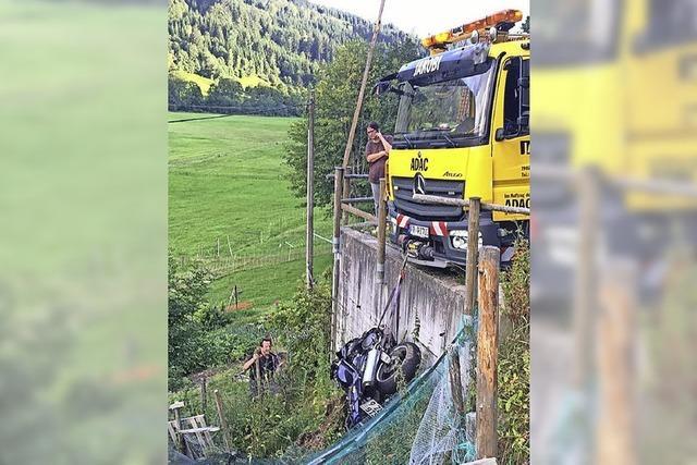 Motorrad schlittert und fällt Mauer hinab