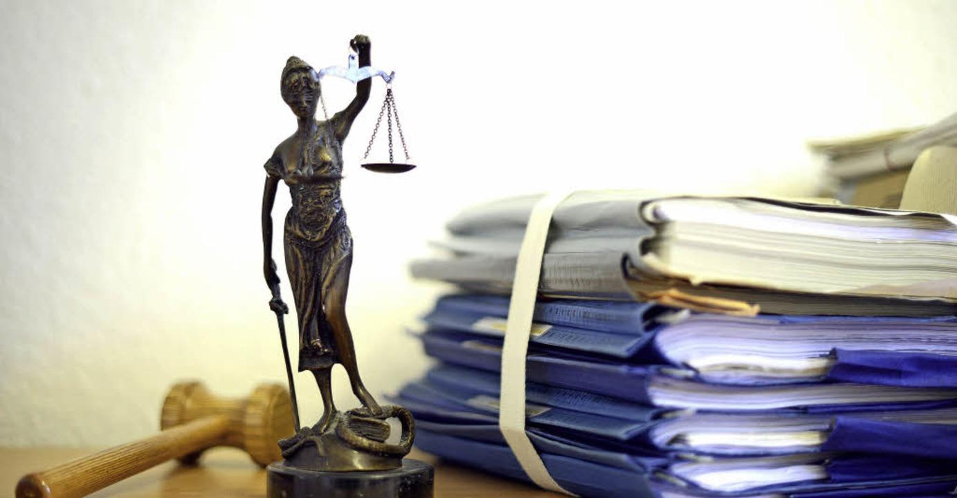Die modellhafte Nachbildung der Justitia steht neben Akten.   | Foto: Dpa