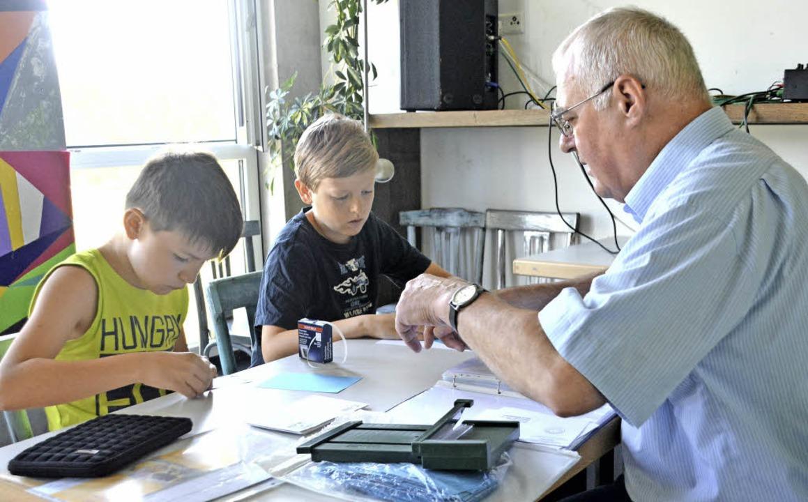 Norbert Amrein erklärt seinen zwei Gästen, wie man richtig Briefmarken sammelt.   | Foto: Danielle Hirscherberger