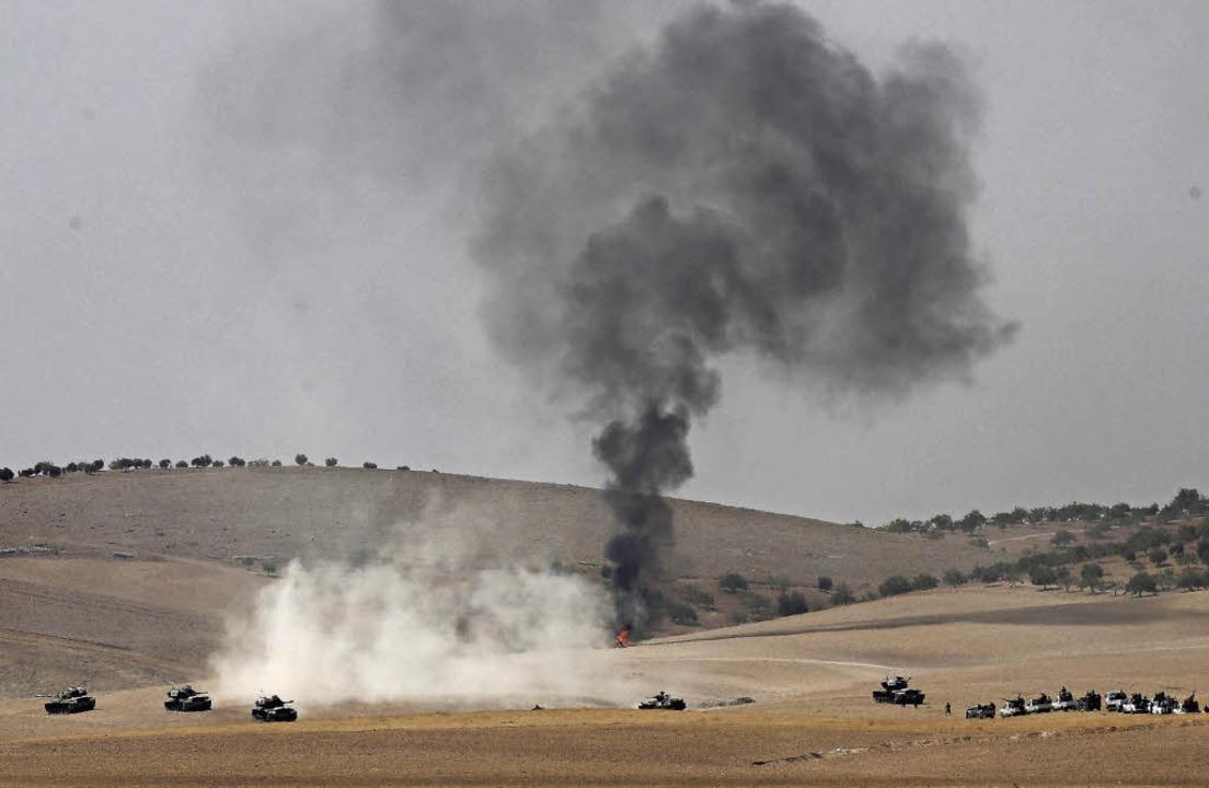 Türkische Panzer überqueren  zusammen ...er Freien Syrischen Armee die Grenze.     Foto: DPA