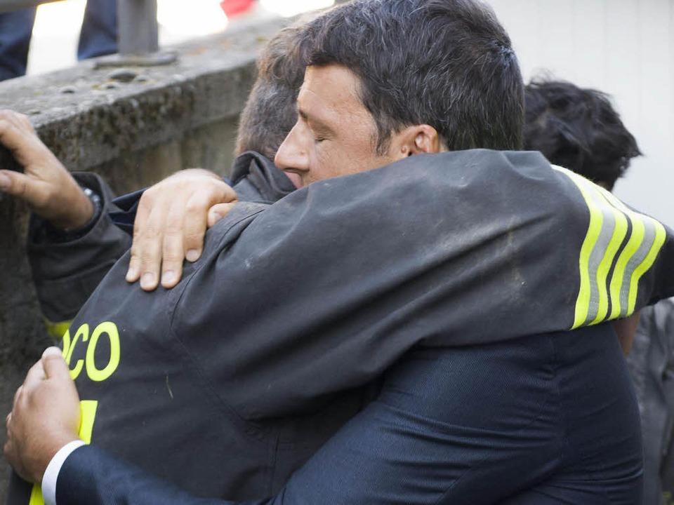 Amatrice – eine Stadt liegt in T...ngschef Renzi umarmt einen der Helfer.  | Foto: dpa