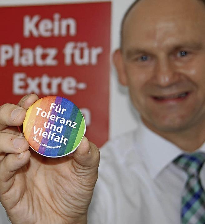 Andreas Rühle präsentiert einen der Buttons der Aktion Miteinander.   | Foto: SENF