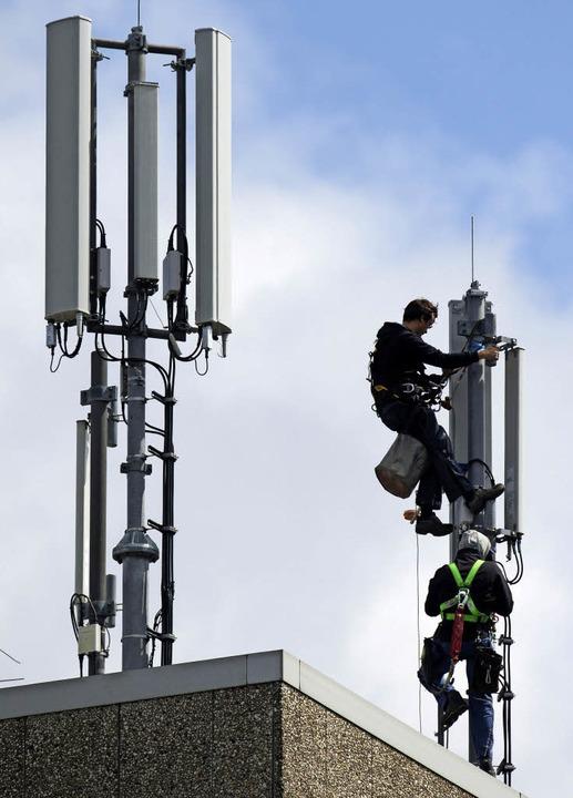 Techniker bei der Arbeit an einem  Mob...n neuen Standort für einen Sendemast.   | Foto: dpa