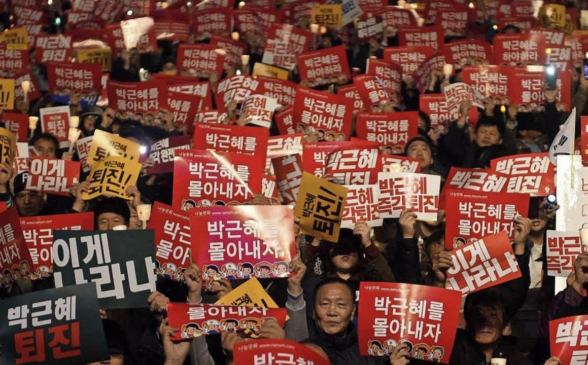 Demonstranten in Seoul fordern den Rücktritt Park Geun-hyes.   | Foto: AFP