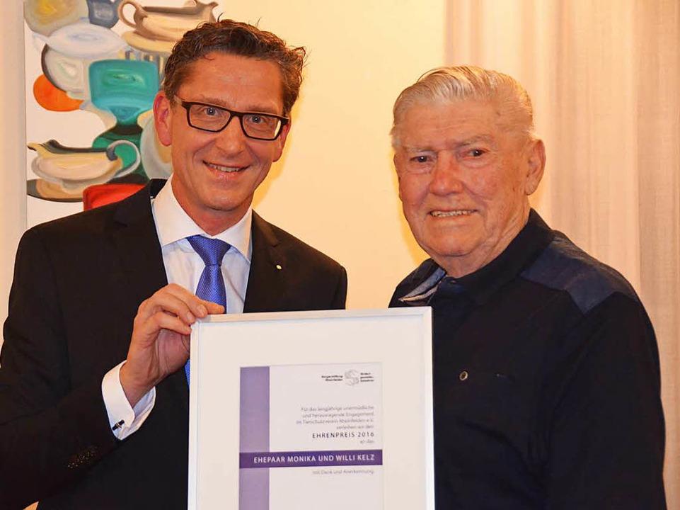Rainer Liebenow überreicht die Urkunde an Willi Kelz  | Foto: Peter Gerigk
