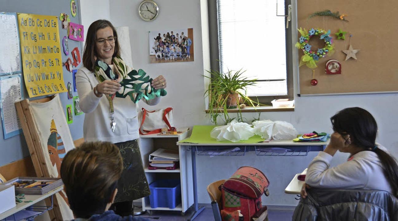Rafaela Olwitz zeigt den Schülern, wie man einen Weihnachtsstern bastelt.  | Foto: Janina Ruth