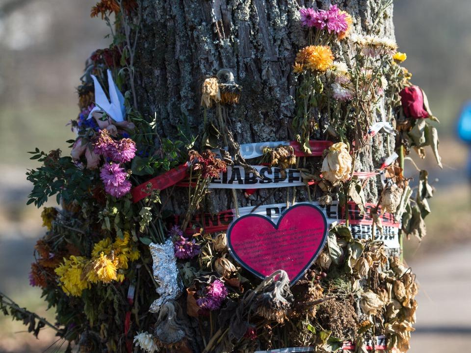 Blumen und Trauerschmuck an einem Baum... Dreisam. Hier wurde Maria L. getötet.  | Foto: dpa