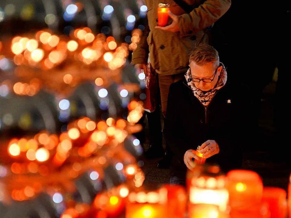 Ein Mann entzündet unweit der Gedächtniskirche eine Kerze    Foto: dpa