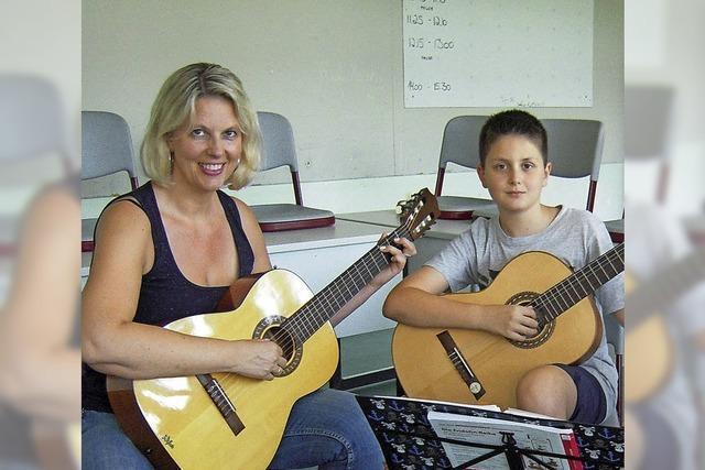 Eltern helfen an der Gitarre