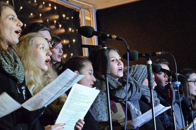 Besucher singen auf Stroh sitzend und unter Sternen mit