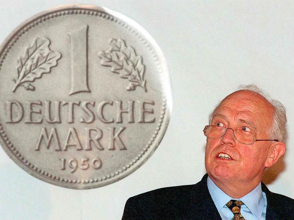 Hans Tietmeyer 1998 vor einem überdimensional großen Abbild der D-Mark   | Foto: dpa