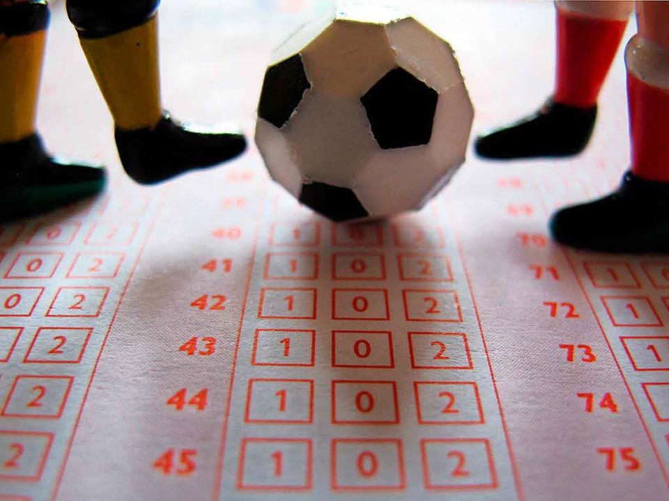 Ein Fußball und vier Spielerfiguren au...in für Fußballbegegnungen (Symbolbild)    Foto: dpa