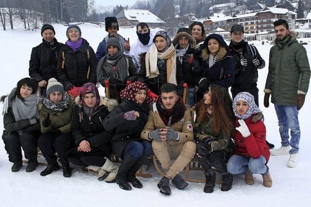 Junge Flüchtlinge genießen das Winterwetter beim Schlittenfahren am Kesslerhang