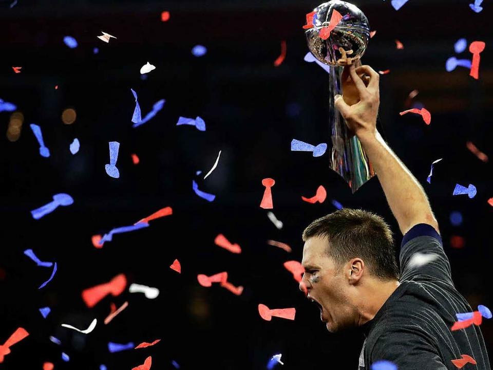 Tom Brady jubelt nach dem Sieg seiner New England Patriots mit dem Pokal.  | Foto: dpa