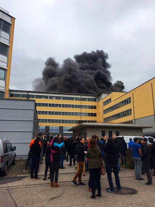 Mitarbeiterinnen und Mitarbeiter versa...m Ausbruch des Feuers vor dem Gebäude.  | Foto: bz